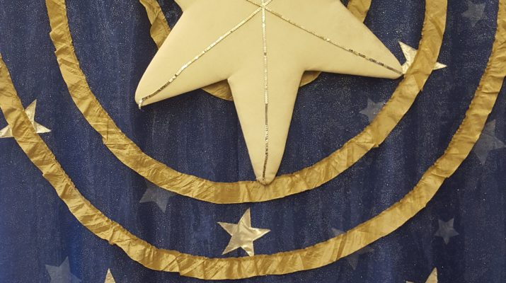 a fabric banner, showing a star over a manger
